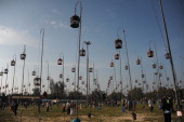 Villagers walk past hanging bird cages during a birdsinging contest in Thailand's southern province of Narathiwat on September 23 2013 Hundreds of...