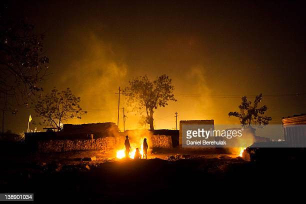 Villagers warm themselves by a fire made of coal scavenged from an opencast coal mine in the village of Guhanwadi on February 09 2012 near Jharia...