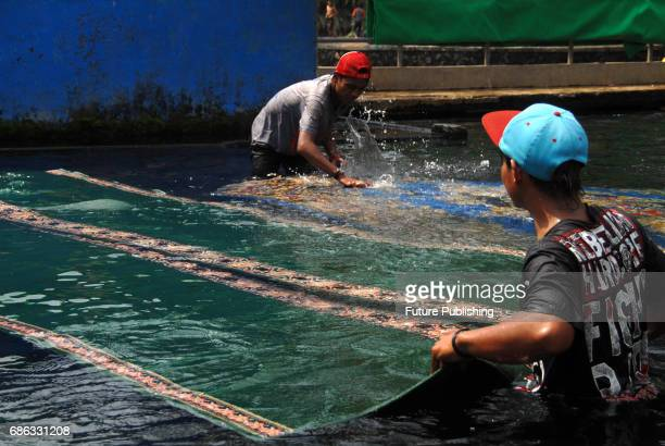 Villagers wash the carpets of a mosque in the pool that became the source of Umbulan springs on May 21 2017 in Pasuruan Indonesia Washing the mosque...