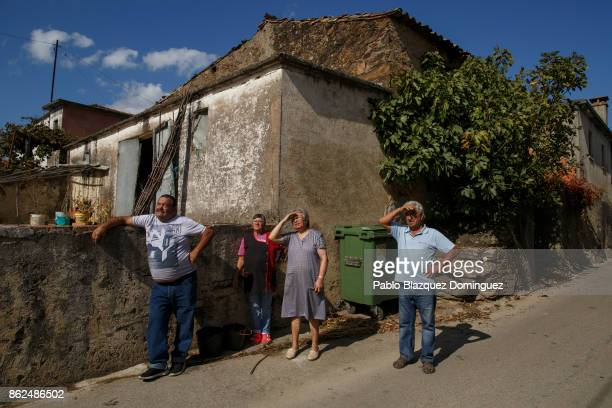 Villagers watch as firefighters try to extinguish a burning house in the village of Travanca do Mondego on October 17 2017 in Coimbra region Portugal...