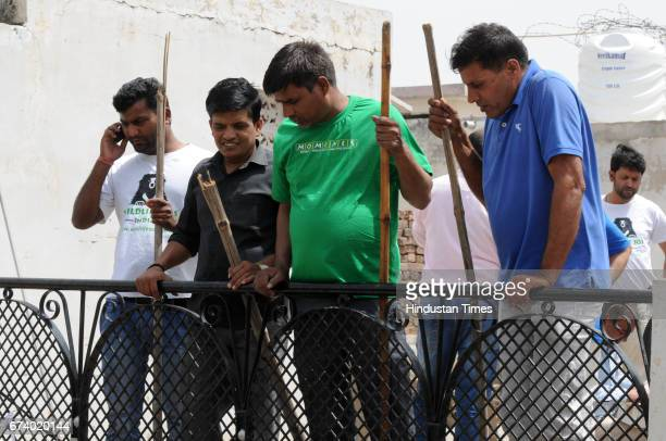 Villagers were seen holding sticks to escape from the leopard attack outside the house where he was trapped on April 27 2017 some 25 km from Gurgaon...