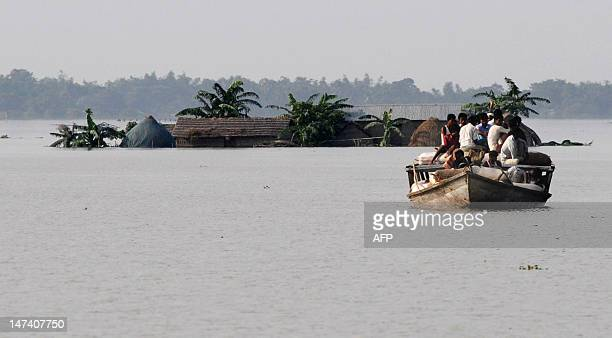 Villages travel on a boat in the flood affected area of Jhargoan village in Morigoan district some 80 kms from Guwahati the capital city of India's...