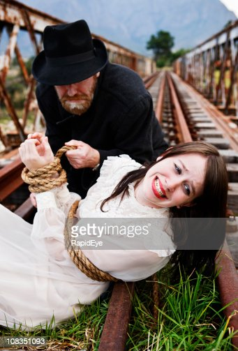 Villain ties desperate maiden to railway track in Victorian melodrama : Stock Photo