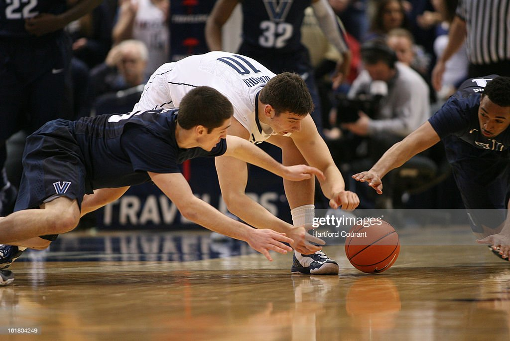 Villanova's Ryan Arcidiacono, left, and Darrun Hilliard, right and Connecticut's Tyler Olander chase a loose ball in the first half at the XL Center in Hartford, Connecticut, Saturday, February 16, 2013. Villanova defeated UConn, 70-61.