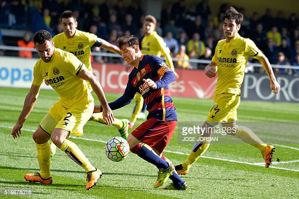 Villarreal's defender Mario vies with Barcelona's Argentinian forward Lionel Messi during the Spanish league football match Villarreal CF vs FC...