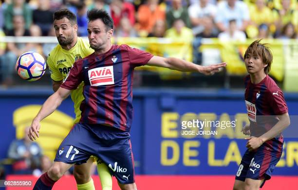 TOPSHOT Villarreal's defender Mario vies with Eibar's forward Kike Garcia beside Eibar's Japanese midfielder Takashi Inui during the Spanish league...