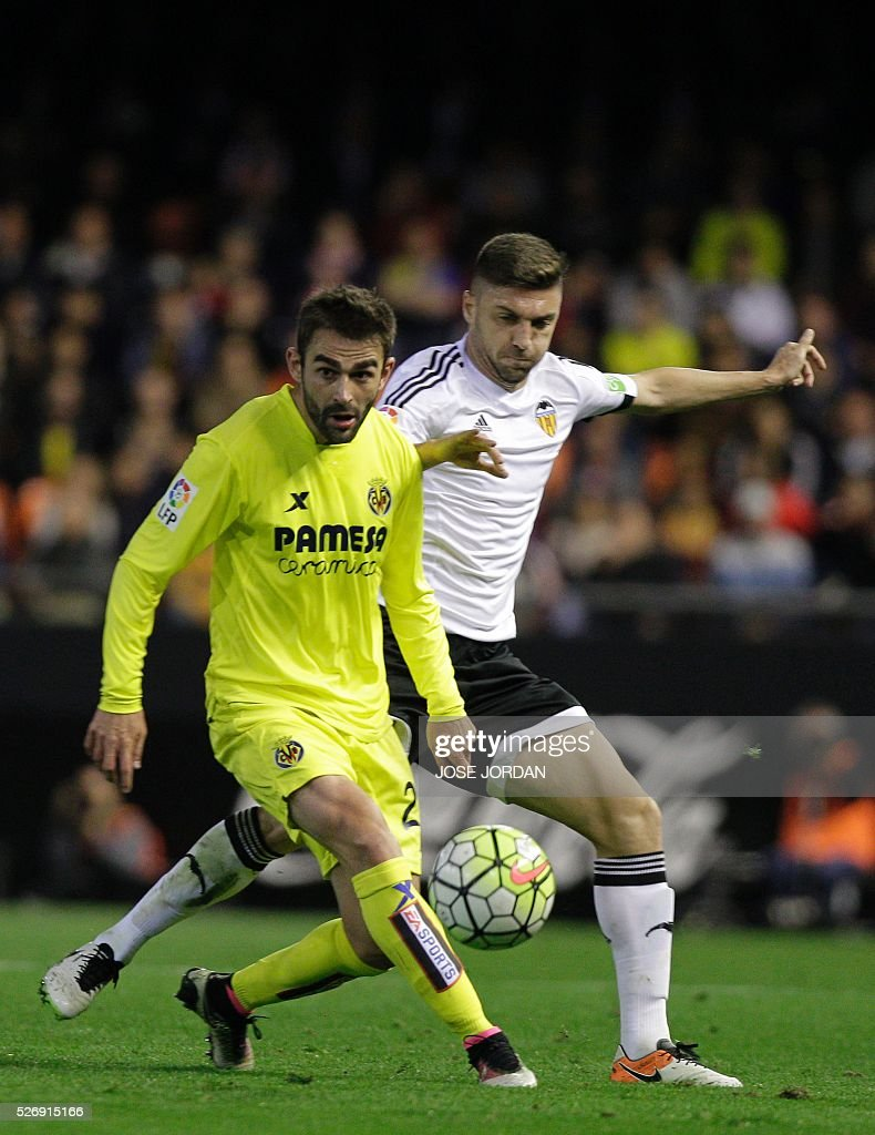 Villarreal's forward Adrian Lopez (L) vies with Valencia's Brazilian defender Guillerme Siqueira during the Spanish league football match Valencia CF vs Villarreal CF at the Mestalla stadium in Valencia on May 1, 2016. / AFP / JOSE