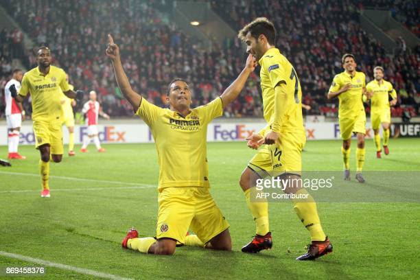 Villarreal's forward from Colombia Carlos Bacca celebrates with teammate midfielder from Spain Manuel Trigueros Munoz after he scored a goal during...