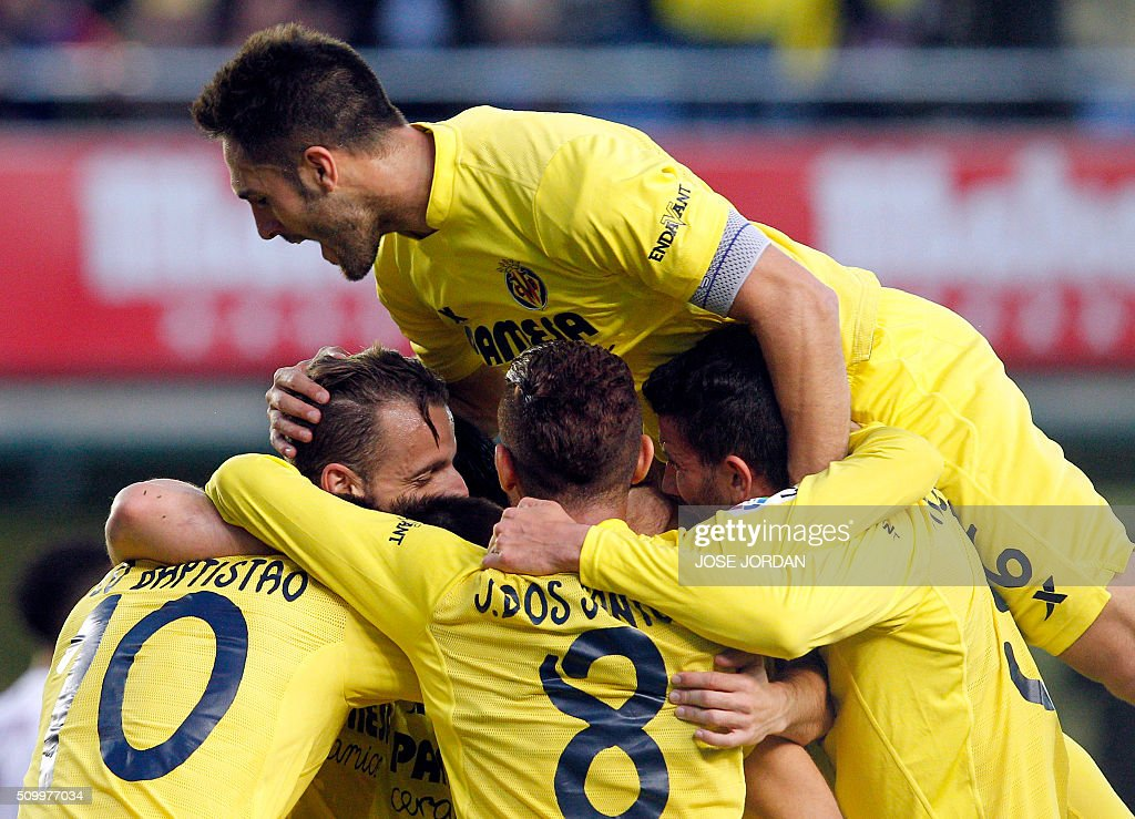 Villarreal's forward Roberto Soldado (L) celebrates a goal with teammates during the Spanish league football match Villarreal CF vs Malaga CF at the at El Madrigal stadium in Vila-real on February 13, 2016. / AFP / Jose Jordan