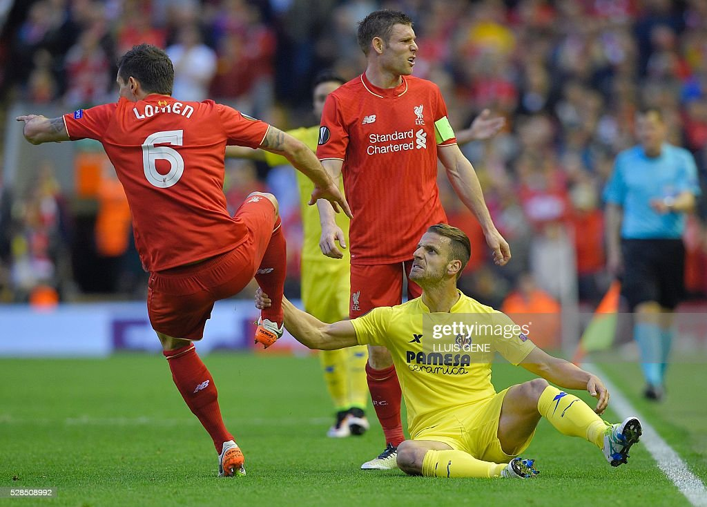 Villarreal's forward Roberto Soldado (Below) holds the leg of Liverpool's Croatian defender Dejan Lovren during the UEFA Europa League semi-final second leg football match between Liverpool and Villarreal CF at Anfield in Liverpool, northwest England on May 5, 2016. / AFP / LLUIS