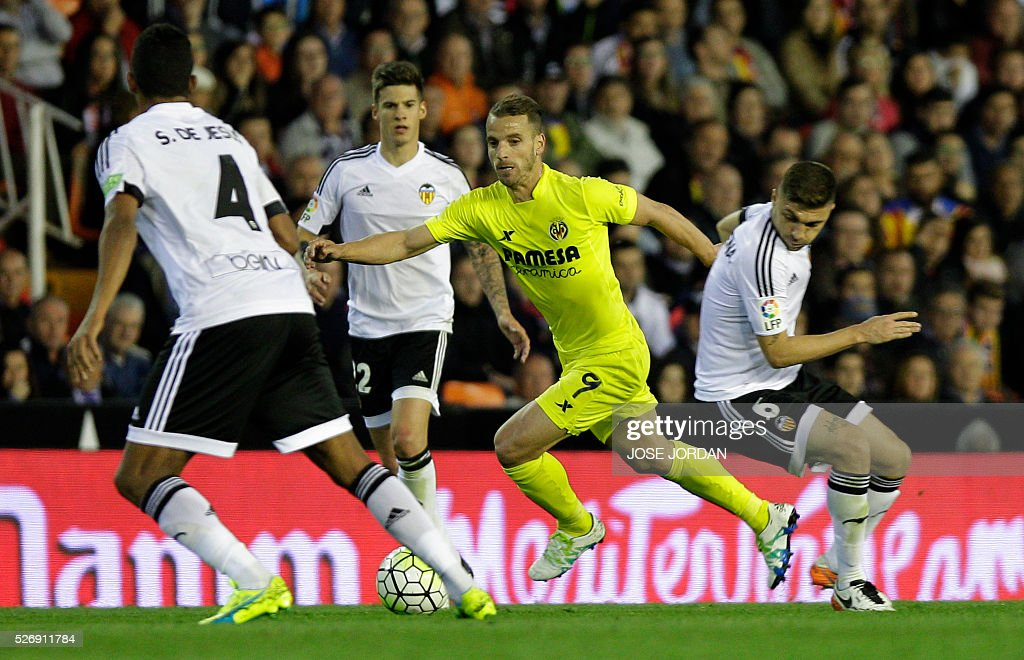 Villarreal's forward Roberto Soldado (L) vies with Valencia's Brazilian defender Guillerme Siqueira during the Spanish league football match Valencia CF vs Villarreal CF at the Mestalla stadium in Valencia on May 1, 2016. / AFP / JOSE