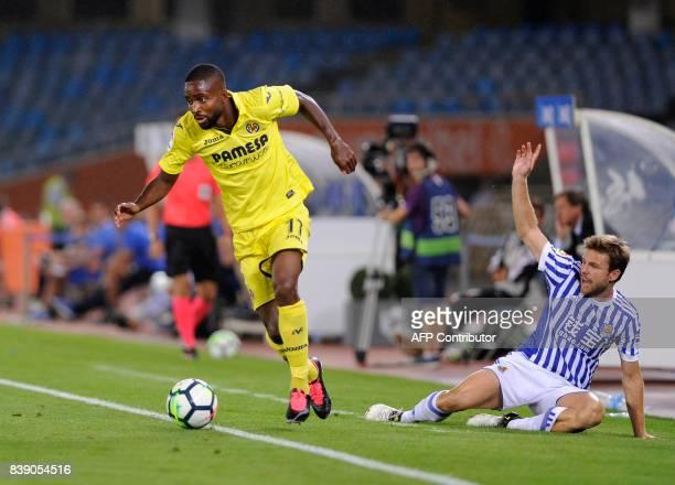 Villarreal's French forward Cedric Bakambu vies with Real Sociedad's midfielder Asier Illarramendi during the Spanish league football match Real...
