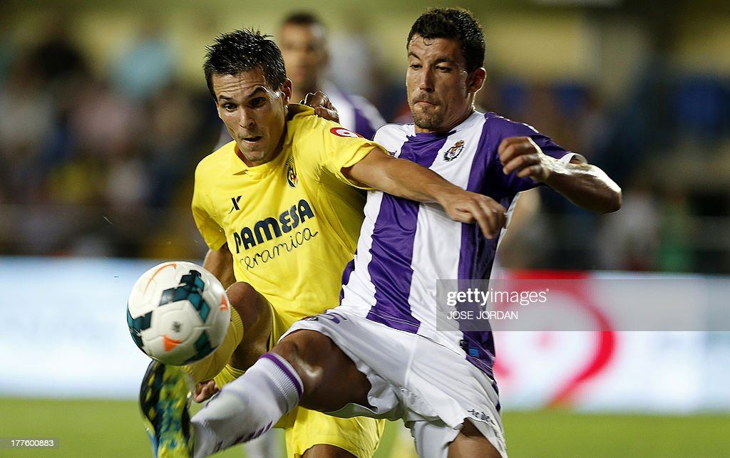 Villarreal's French forward Jeremy Perbet (L) vies with Valladolid's midfielder Lluis Sastre during the Spanish league football match Villarreal CF vs Real Valladolid FC de Madrid at El Madrigal stadium in Villareal on August 24, 2013.