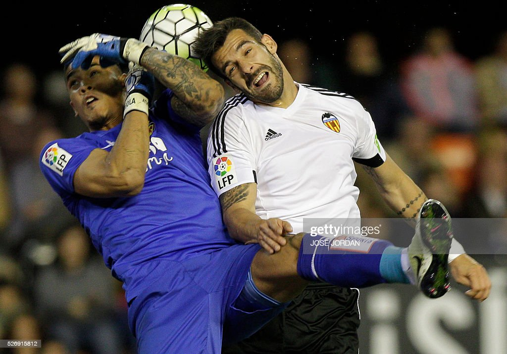 Villarreal's French goalkeeper Alphonse Areola (L) vies with Valencia's forward Alvaro Negredo during the Spanish league football match Valencia CF vs Villarreal CF at the Mestalla stadium in Valencia on May 1, 2016. / AFP / JOSE