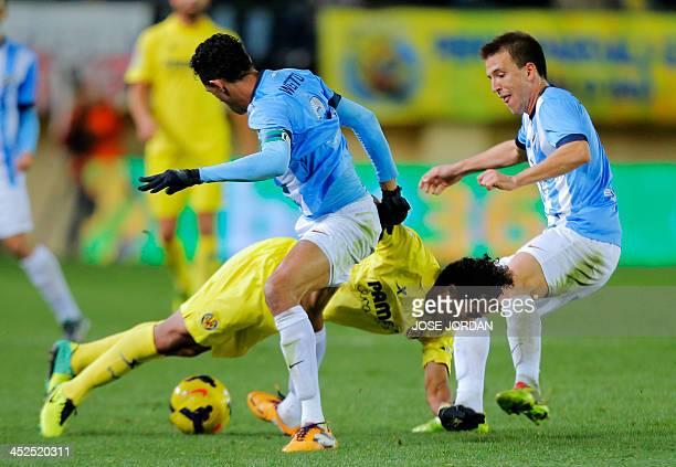 Villarreal's Mexican forward Giovani Dos Santos vies with Malaga's Brazilian defender Weligton and Malaga's midfielder Ignacio Camacho during the...
