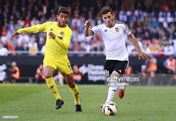 Villarreal's Mexican midfielder Jonathan dos Santos Ramirez vies with Valencia's defender Jose Gaya during the Spanish league football match Valencia...