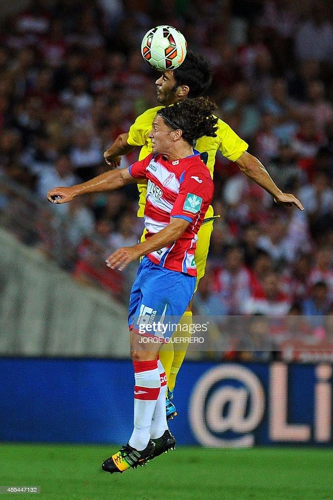 Villarreal's midfielder Manuel Trigueros vies with Granada's Chilean midfielder Manuel Iturra during the Spanish league football match Granada CF vs...