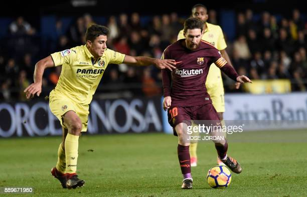 Villarreal's midfielder Rodrigo Hernandez vies with Barcelona's Argentinian forward Lionel Messi during the Spanish league football match between...