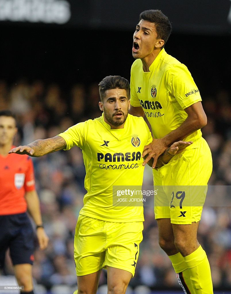 Villarreal's midfielder Samuel Garcia (L) celebrates with Villarreal's forward Adrian Lopez after scoring during the Spanish league football match Valencia CF vs Villarreal CF at the Mestalla stadium in Valencia on May 1, 2016. / AFP / JOSE