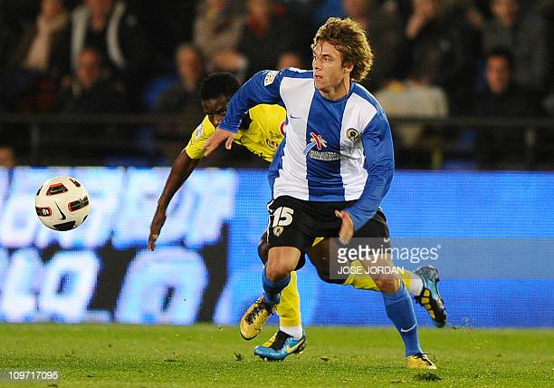 Villarreal's midfielder Wakaso vies for the ball with Hercules' defender Kiko Femenia during the Spanish league football match Villareal CF vs...