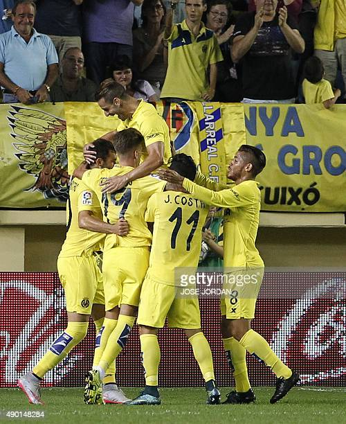 Villarreal's players celebrate their first goal during the Spanish league football match Villarreal CF vs Club Atletico de Madrid at El Madrigal...