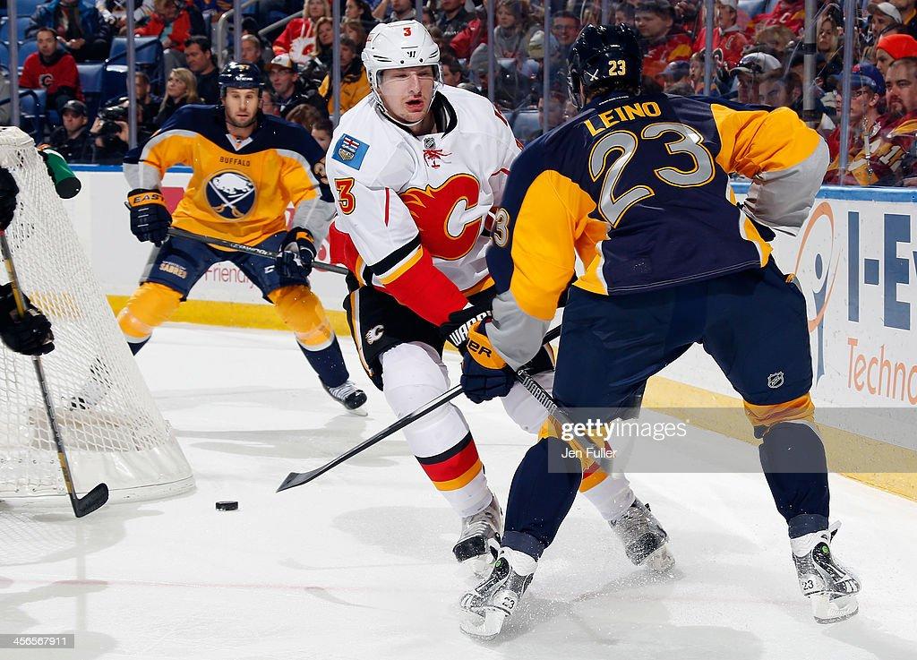 Ville Leino #23 of the Buffalo Sabres battles behind the net with Ladislav Smid #3 of the Calgary Flames as teammate Matt Ellis #37 follows the play at First Niagara Center on December 14, 2013 in Buffalo, New York.
