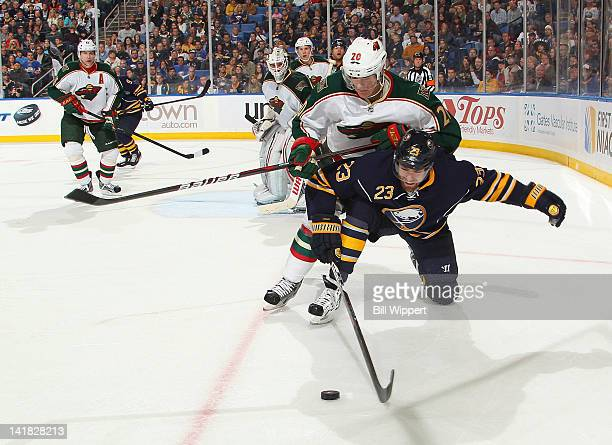 Ville Leino of the Buffalo Sabres gets checked by Kurtis Foster of the Minnesota Wild at First Niagara Center on March 24 2012 in Buffalo New York