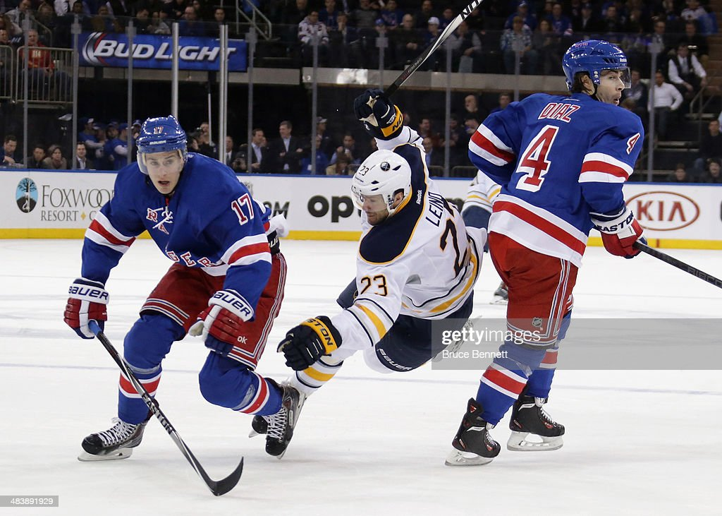 Ville Leino #23 of the Buffalo Sabres is tripped up during the first period against John Moore #17 and Raphael Diaz #4 of the New York Rangers at Madison Square Garden on April 10, 2014 in New York City.