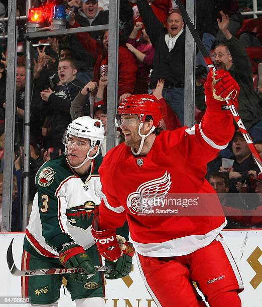 Ville Leino of the Detroit Red Wings celebrates his 2nd period goal as Marek Zidlicky of the Minnesota Wild looks on during their NHL game at Joe...