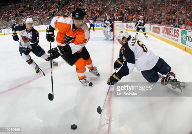 Ville Leino of the Philadelphia Flyers battles in the corner for the loose puck with Alexander Burmistrov and Ron Hainsey of the Atlanta Thrashers on...