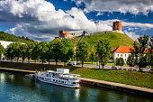 Sightseeing boat on the Neris River with ruins of Gediminas castle, Vilnius, Lithuania