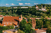 Vilnius, Lithuania. View Of Church Of St. Anne, Church of St. Francis and St. Bernard, Church Of Ascension And Church Of Sacred Heart Of Jesus Among Green Foliage In Old Town In Summer Day.