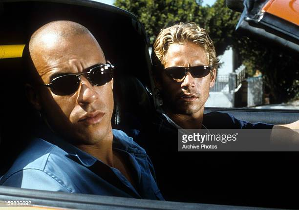 Vin Diesel and Paul Walker looking from car in a scene from the film 'The Fast And The Furious' 2001
