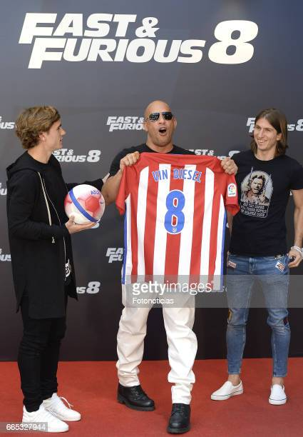 Vin Diesel receives an Atletico de Madrid shirt from Atletico de Madrid players Antoine Griezmann and Filipe Luis during a photocall for 'Fast and...