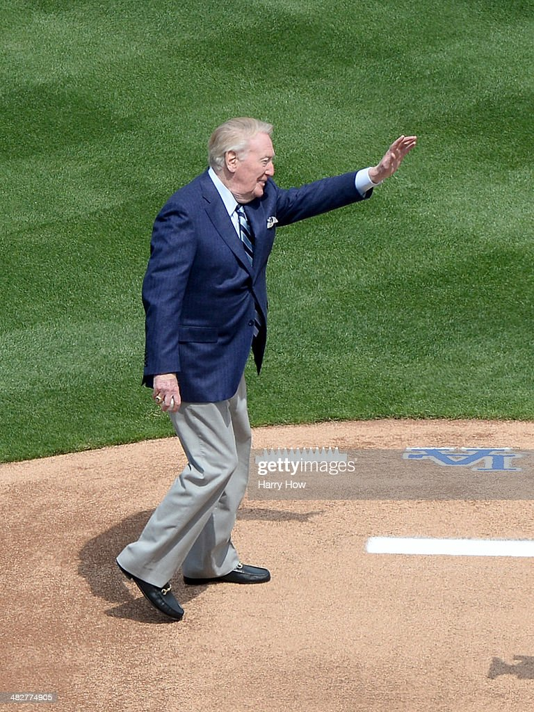 Vin Scully waves to fans as he takes to the mound to throw out a ceremonial first pitch before the game between the San Francisco Giants and the Los...