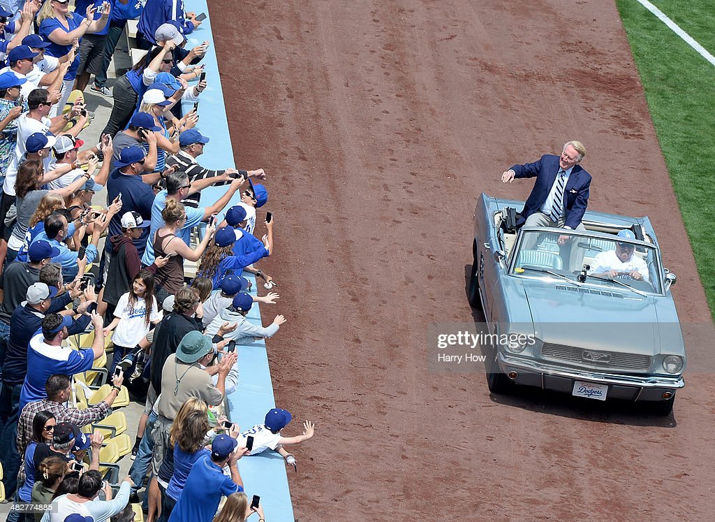 Vin Scully waves to fans from a car before the game between the San Francisco Giants and the Los Angeles Dodgers on opening day at Dodger Stadium on...