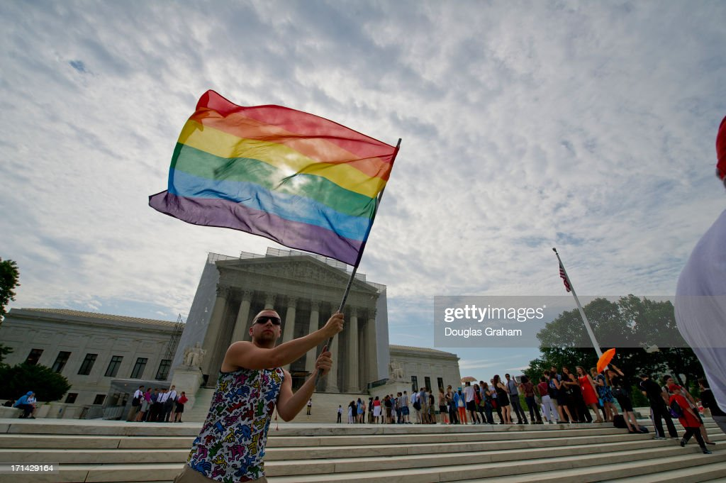 Vin Testa a gay rights activist waves a flag in front of the U.S. Supreme Court building June 24, 2013 in Washington DC. The high court is expected to rule this week on some high profile decisions including California's Proposition 8, the controversial ballot initiative that defines marriage as between a man and a woman.