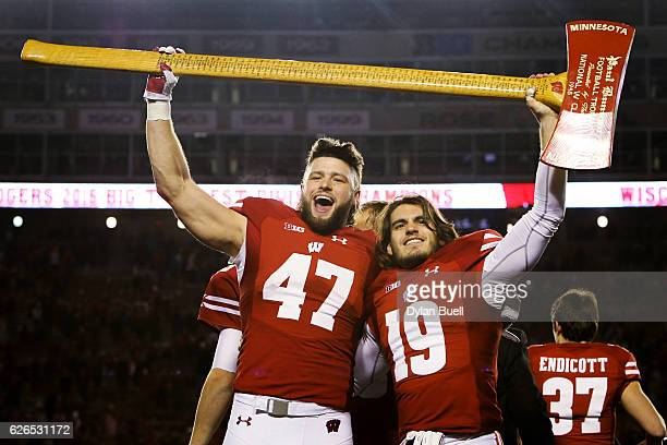 Vince Biegel and Leo Musso of the Wisconsin Badgers hoist the Paul Bunyan's Axe trophy after beating the Minnesota Golden Gophers 3117 at Camp...