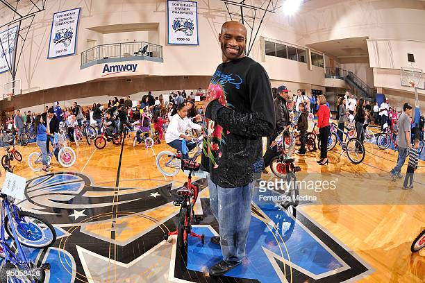 Vince Carter of Orlando Magic reacts with a smile after delivering bikes to children during a holiday party for 42 families from Apopka Family...