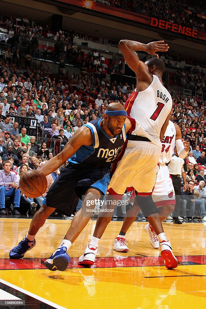 Vince Carter #25 of the Dallas Mavericks drives to the basket against Chris Bosh #1 of the Miami Heat on January 2, 2013 at American Airlines Arena in Miami, Florida.