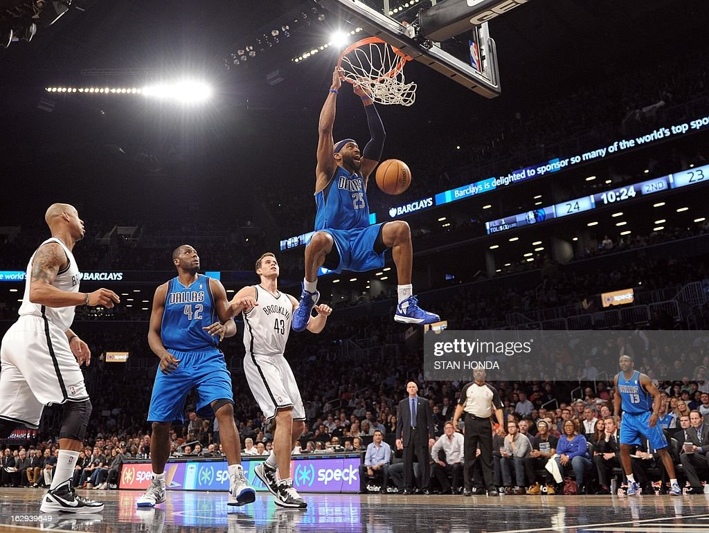 Vince Carter (R) of the Dallas Mavericks dunks against Kris Humphries (2R) of the Brooklyn Nets as Elton Brand (2L) of the Mavericks watches at the Barclays Center March 1, 2013 in the Brooklyn borough of New York. AFP PHOTO/Stan HONDA