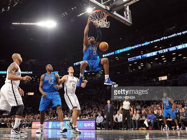 Vince Carter of the Dallas Mavericks dunks against Kris Humphries of the Brooklyn Nets as Elton Brand of the Mavericks watches at the Barclays Center...