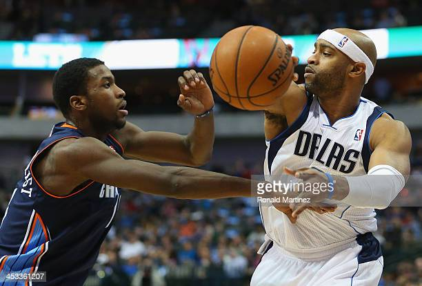 Vince Carter of the Dallas Mavericks passes the ball against Michael KiddGilchrist of the Charlotte Bobcats at American Airlines Center on December 3...