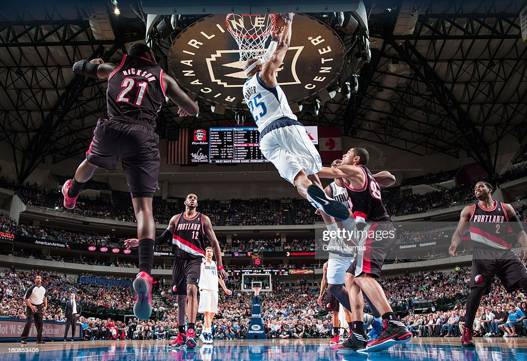 Vince Carter #25 of the Dallas Mavericks throws down the reverse dunk against J.J. Hickson #21 and Nicolas Batum #88 of the Portland Trail Blazers on February 6, 2013 at the American Airlines Center in Dallas, Texas.