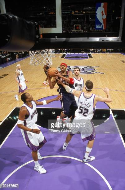 Vince Carter of the New Jersey Nets attempts to shoot against Brad Miller and Cuttino Mobley of the Sacramento Kings during the game at Arco Arena on...