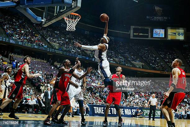 Vince Carter of the New Jersey Nets dunks against Chris Bosh of the Toronto Raptors in Game Six of the Eastern Conference Quarterfinals during the...