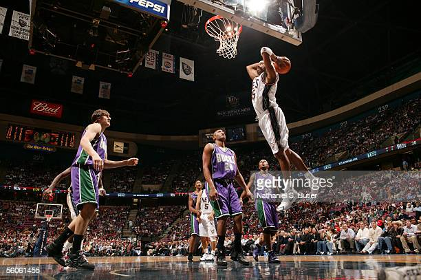 Vince Carter of the New Jersey Nets dunks against Jamaal Magloire of the Milwaukee Bucks at the Continental Airlines Arena on November 2 2005 in East...