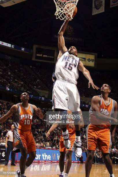 Vince Carter of the New Jersey Nets dunks against Kurt Thomas and Leandro Barbosa of the Phoenix Suns December 7 2006 at the Continental Airlines...