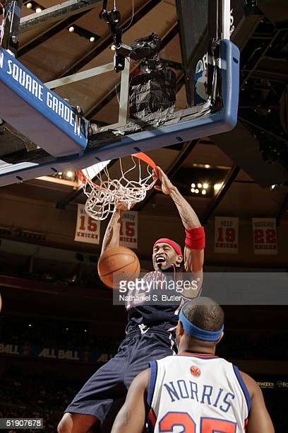 Vince Carter of the New Jersey Nets dunks against Moochie Norris of the New York Knicks at Madison Square Garden on January 1 2005 in New York City...