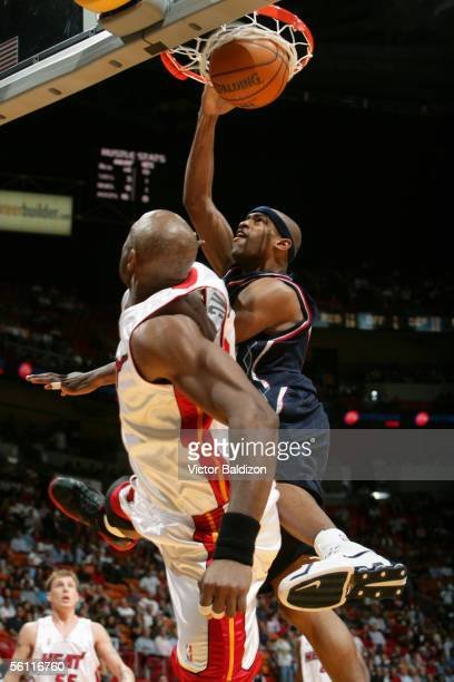 Vince Carter of the New Jersey Nets dunks over Alonzo Mourning of the Miami Heat November 7 2005 at American Airlines Arena in Miami Florida NOTE TO...